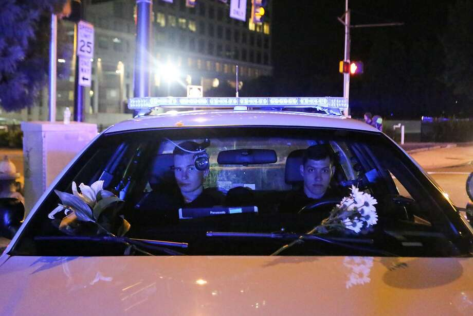 Police officers with flowers on the windshield of their cruiser, stationed at an intersection in Charlotte, N.C., Sept. 23, 2016. Faced with mounting demands for transparency, CharlotteÕs leaders resisted calls on Friday for the immediate release of video of the shooting death of Keith Scott. (Logan R. Cyrus/The New York Times) Photo: LOGAN R. CYRUS, NYT