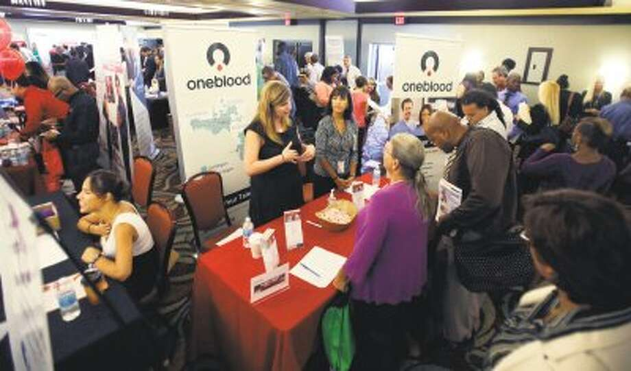 Job seekers check out opportunities during a job fair in Miami Lakes, Fla on Aug. 14. U.S. employers added 169,000 jobs in August, and the unemployment rate dropped to 7.3 percent, the lowest in nearly five years, according to the Labor Department, Friday, Sept. 6.