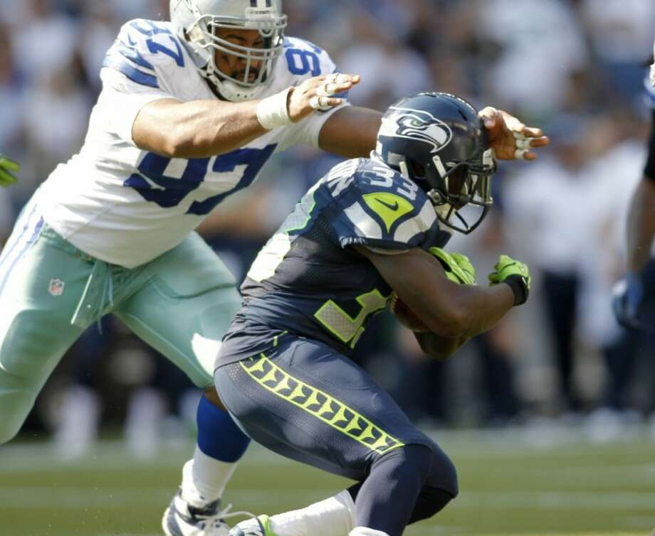 The Seahawks' Leon Washington, right, dodges Jason Hatcher of the Cowboys. The Seahawks won 27-7. Photo: John Froschauer