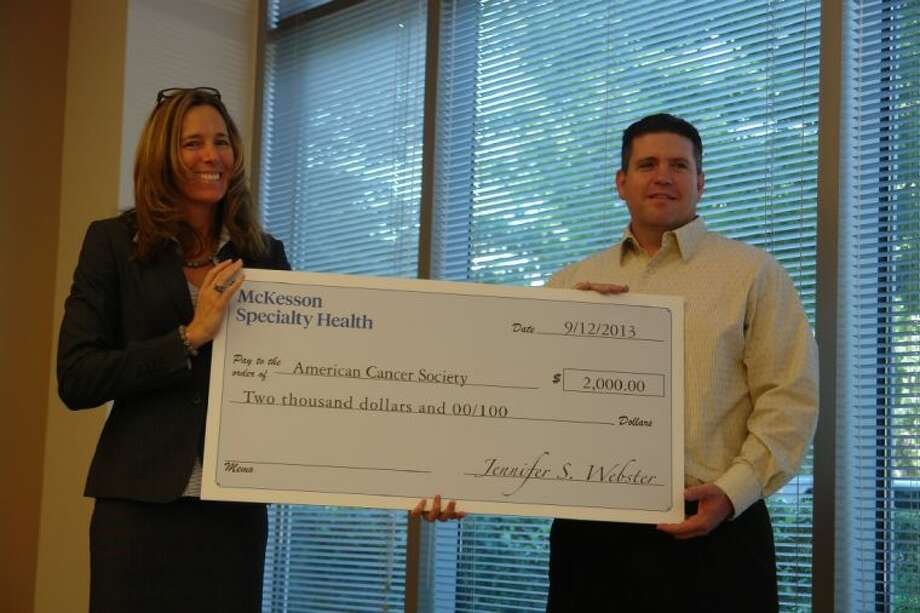 McKesson CFO Jennifer Webster hands a $2,000-check to Daryl Hayes of the American Cancer Society. The money is part of an award McKesson Specialty Health in The Woodlands received for its environmental council.