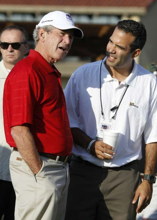 Former President George W. Bush, left, talks with talks with his nephew George P. Bush during the Bush Center Warrior Open in Irving, Texas, Monday. The Warrior Open is a two-day golf tournament featuring members of the U.S. Armed Forces who were severely wounded during the global war against terrorism. Photo: LM Otero