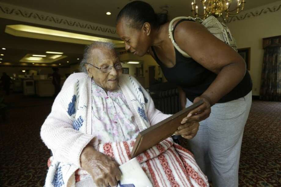 In this Tuesday, July 30, 2013 photo, Jacquelin Finley, right, shows her grandmother Ida Filey, 101, a family photo she recovered during a visit to the house she grew up in with her grandmother in Dirgin, Texas. The Finleys are descendants of slaves holding out against company's attempt to mine East Texas land for coal. Photo: LM Otero