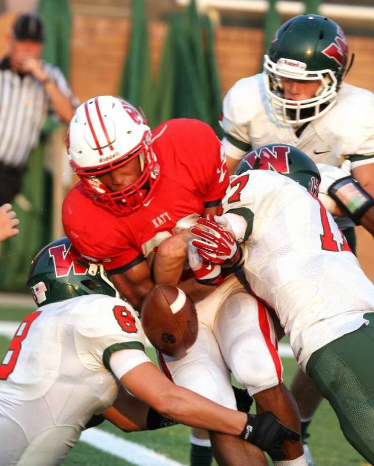 Katy's Rodney Anderson crosses the goal line but fumbles against The Woodlands' Kade Markle. Katy won 37-14. Photo: Photo By Alan Warren