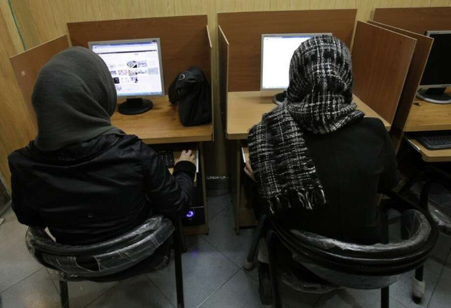 In this Feb. 13, 2012 file photo, Iranian women use computers at an Internet cafe in central Tehran. Iran's cyber monitors often tout their efforts to fight the West's 'soft war' of influence through the web, but trying to ban Google's popular Gmail may have gone too far with complaints coming even from email-starved parliament members. Photo: Vahid Salemi