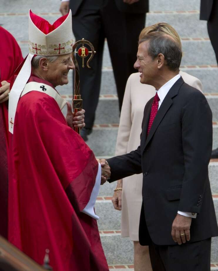 Cardinal Archbishop of Washington Donald Wuerl shake hands with U.S. Supreme Court Chief Justice John G. Roberts after the 60th annual Red Mass at the Cathedral of St. Matthew the Apostle in Washington Sunday. The Red Mass is traditionally held in Washington the day before the Supreme Court's new term opens. Photo: Jose Luis Magana