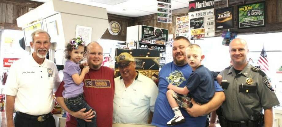 "Montgomery County Precinct 4 Justice of the Peace James Metts, left, and Constable Kenneth ""Rowdy"" Hayden, right, are pictured with members of the Overall family (second from left to right: Ricky Overall, a photo of the late Floyd Overall on cardboard and Jason Overall) at the family's story, Overall Grocery in New Caney. The family has joined the elected officials' ""Do Your Part"" program to battle illegal drug use in East Montgomery County."