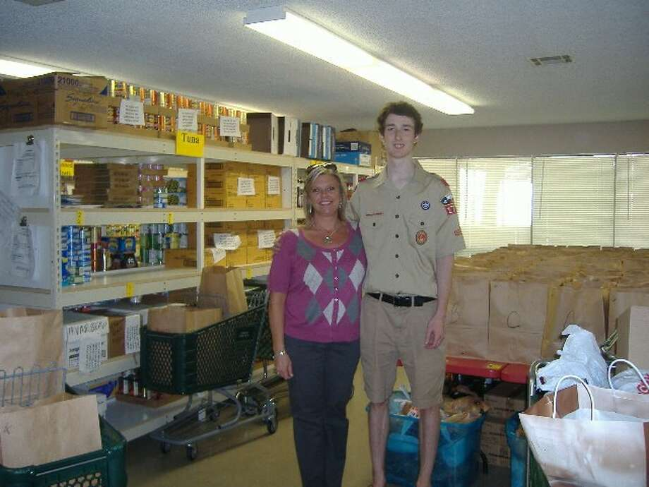 Kathy Rifaat, programs and services director for Interfaith of The Woodlands, stands with new Eagle Scout Clarke Cagle, among the record-setting pounds of nonperishable food items Cagle collected as part of his Eagle Scout project.