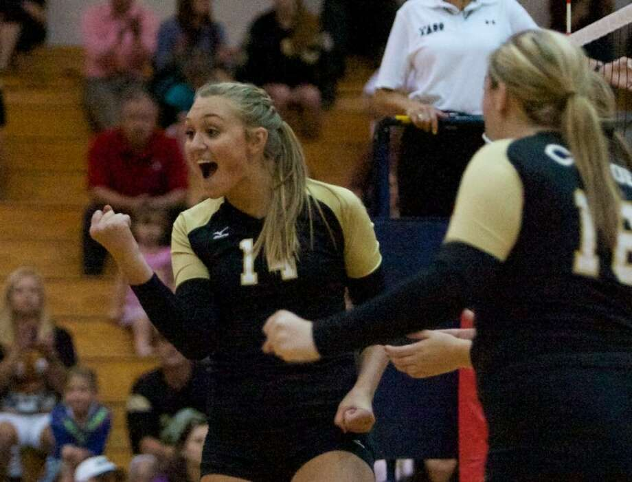 Conroe outside hitter Aubrey Harrison celebrates a point with teammates during Tuesday night's district game against The Woodlands at The Woodlands High School. To view or purchase this photo and others like it visit: www.yourconroenews.com/photos