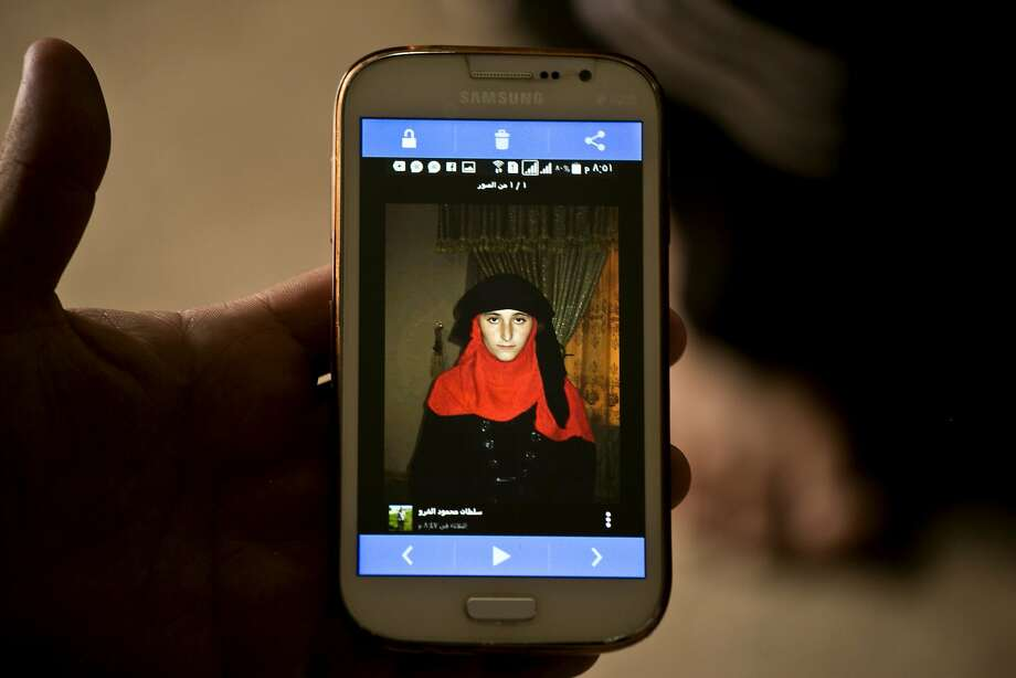 The family of a Yazidi girl enslaved by the Islamic State looks at her photo on a database put together by the group. Investigators believe the group has kidnapped thousands as sex slaves. Photo: Maya Alleruzzo, Associated Press