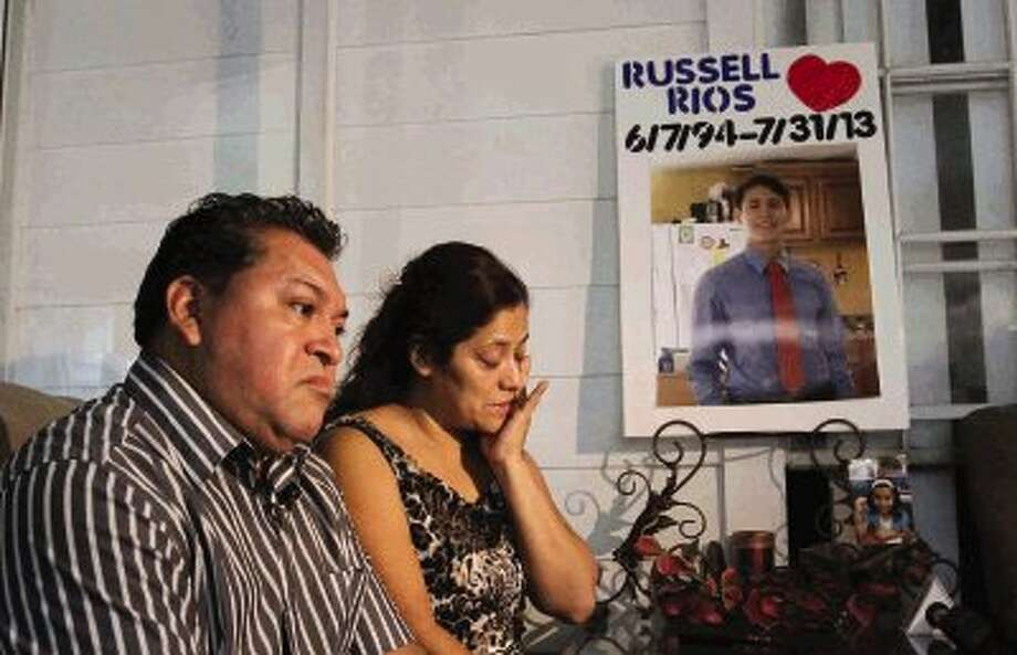 Juan Cuyun and Jacqueline Rios look up at a screen showing a video of their son, Russell Rios, while answering questions from the media Friday. Conroe Police Sgt. Jason Blackwelder allegedly fatally shot Rios in the back of the head after an altercation at Walmart July 31. A Montgomery County grad jury indicted Blackwlder Thursday on one count of manslaughter, one count of tampering with a government document and one count of false report to a police officer. Photo: Staff Photo By Jason Fochtman