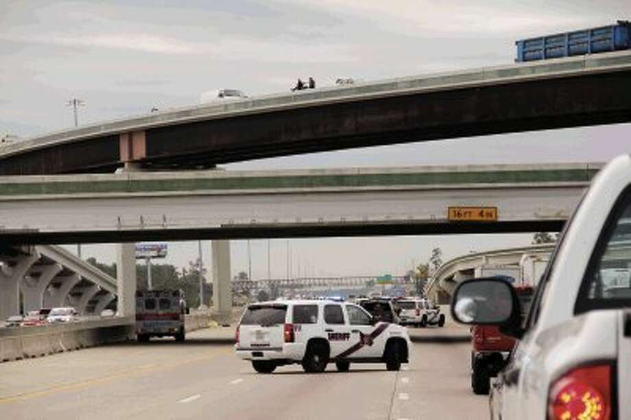Law enforcement officers investigate where Spring resident Larry Dean Asher, 63, fell from The Woodlands Parkway flyover Thursday morning while trying to change a tire. Asher was pronounced dead on the scene. Photo: Staff Photo By James Ridgway, Jr. / James Ridgway, Jr.