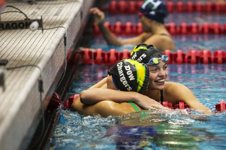 THEOPHIL SYSLO | For the Daily News Dow High School junior Sarah Saead and freshman Claire Newman embrace after competing in the 50 yard freestyle during the 2016 girls swimming and diving Tri-City Championships at Saginaw Valley State University on Saturday. Photo: Theophil Syslo For The Daily News