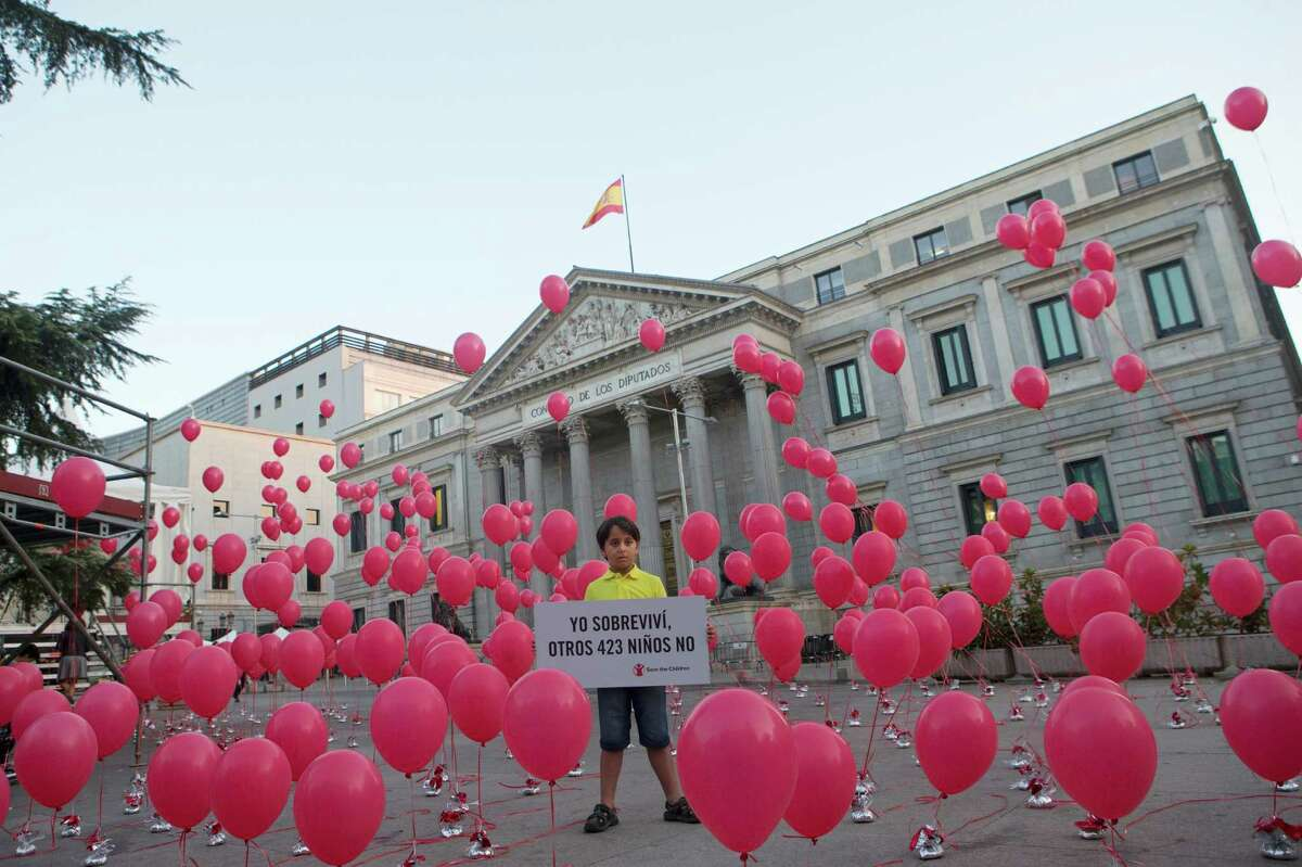 """Zaid, 8, a Syrian refugee now living in Spain, displays a sign in Spanish that reads, """"I survived, 423 other children did not,"""" in front of the Spanish Parliament in Madrid earlier this month. The symbolic protest was to highlight the plight of Syrian refugee children."""