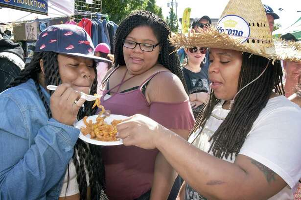 Friends, from left, Nyke Middleton, Maria Drumgoole and Nef Scott share curly fries during the 35th Annual LarkFest, New YorkOs largest one-day street festival, Saturday Sept. 24, 2016 in Albany, NY.  (John Carl D'Annibale / Times Union)