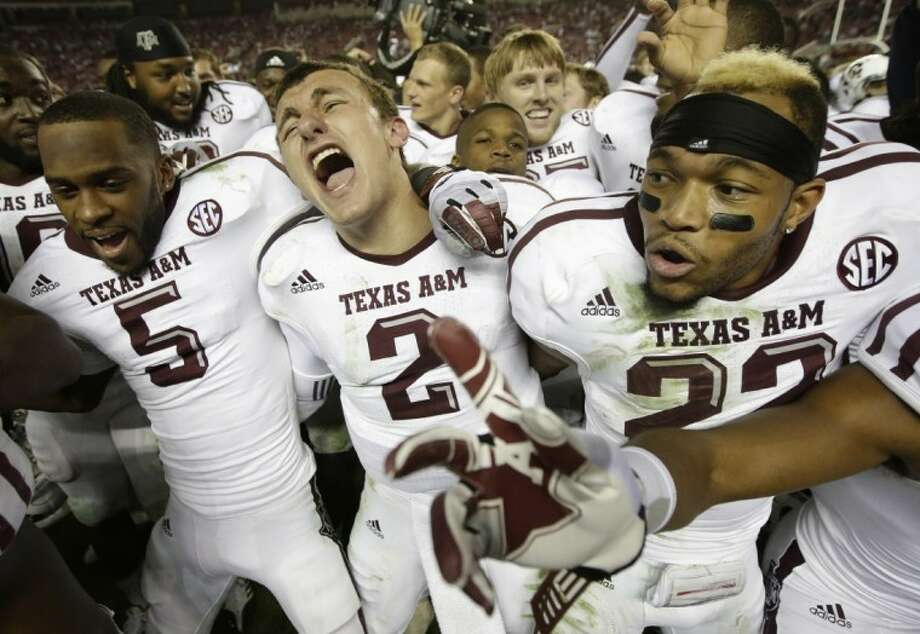 """Texas A&M quarterback Johnny Manziel (2) is joined by teammates Kenric McNeal, left, and Dustin Harris during the """"Aggie War Hymn,"""" after A&M's 29-24 upset of No. 1-ranked Alabama. Photo: Dave Martin"""