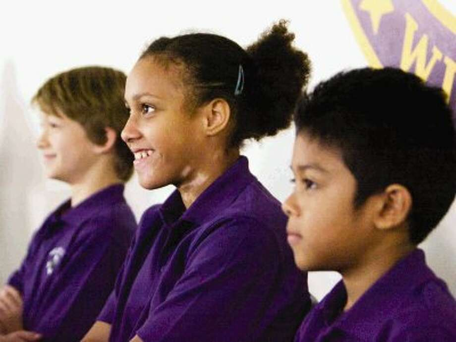 Willis Independent School District students, from left, Crash Nesom, Keely Wilson and Edin Inestroza smile as they interact with NASA astronauts Sunita Williams and Kevin Ford during a video conference Thursday as part of the International Education Week and the Student Spaceflight Experiment Program. The video conference included over 9,500 students from across 24 communities in the U.S. and Canada. Photo: Eric Swist / AP