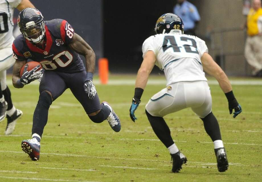 Houston Texans receiver Andre Johnson looks for room to run while the Jaguars' Chris Prosinski (42) defends. Johnson's 48-yard scoring play on a screen pass sent the Texans to a 43-37 victory in overtime. Photo: Dave Einsel
