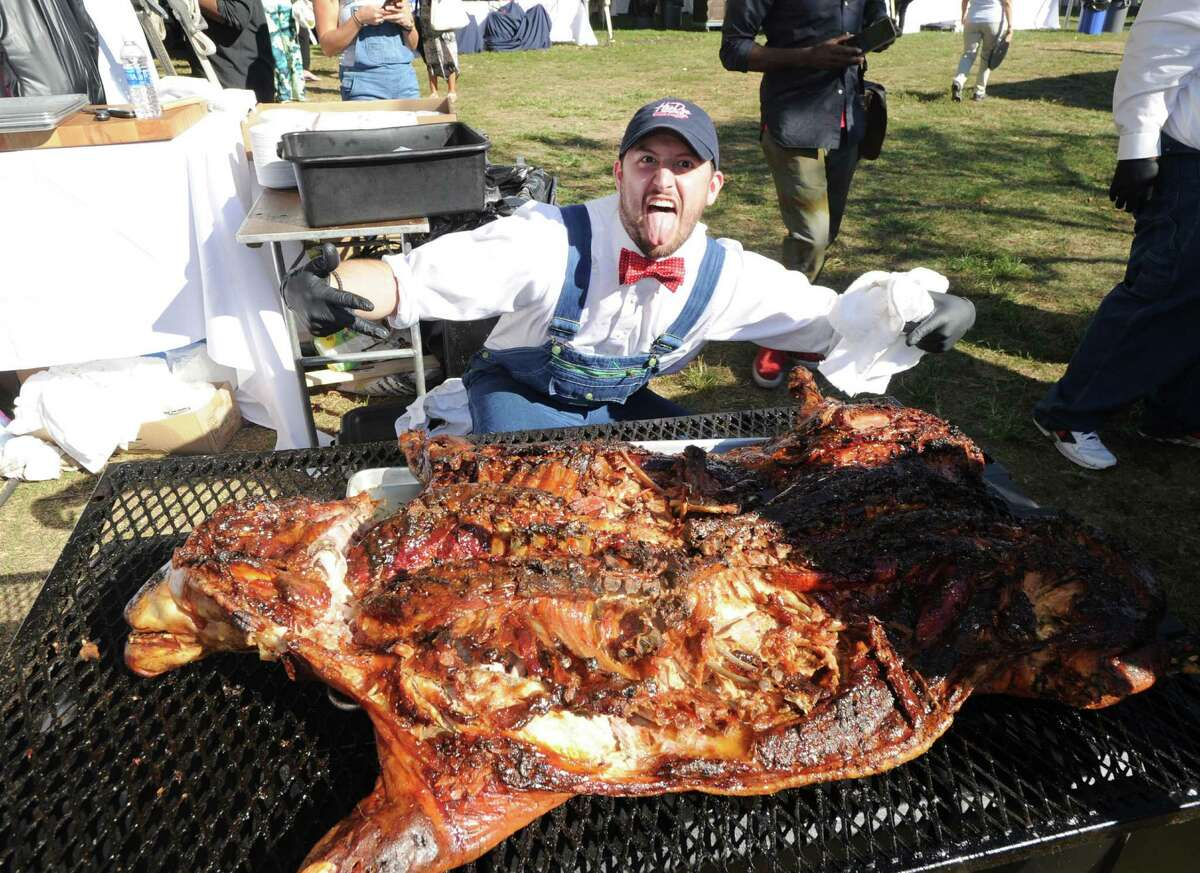 Hoodoo Barbeque Restaurant of Ridgefield grillmaster Mike Peckham busted a move after he and fellow workers finished roasting a 130 pound pig during the Greenwich Wine & Food Festival at Roger Sherman Baldwin Park in Greenwich, Conn., Saturday, Sept. 24, 2016. The annual event benefited Paul Newman's Hole in the Wall Gang Camp, Wholesome Wave and the Greenwich Department of Parks and Recreation, featured a Culinary Village with food and beverage tastings from 90-plus vendors, live music headlined by Ziggy Marley and celebrity chef cooking demonstrations and tastings.