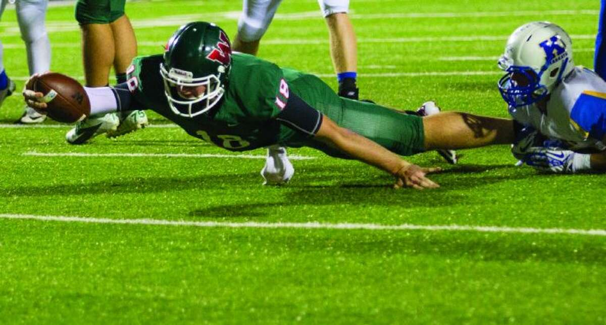 The Woodlands quarterback Chris Andritsos leaps toward the end zone before being tackled by a Klein defender. The Highlanders won 34-31 in overtime at Woodforest Bank Stadium in Shenandoah. Go to HCNPics.com to view and purchase this photo, and others like it.