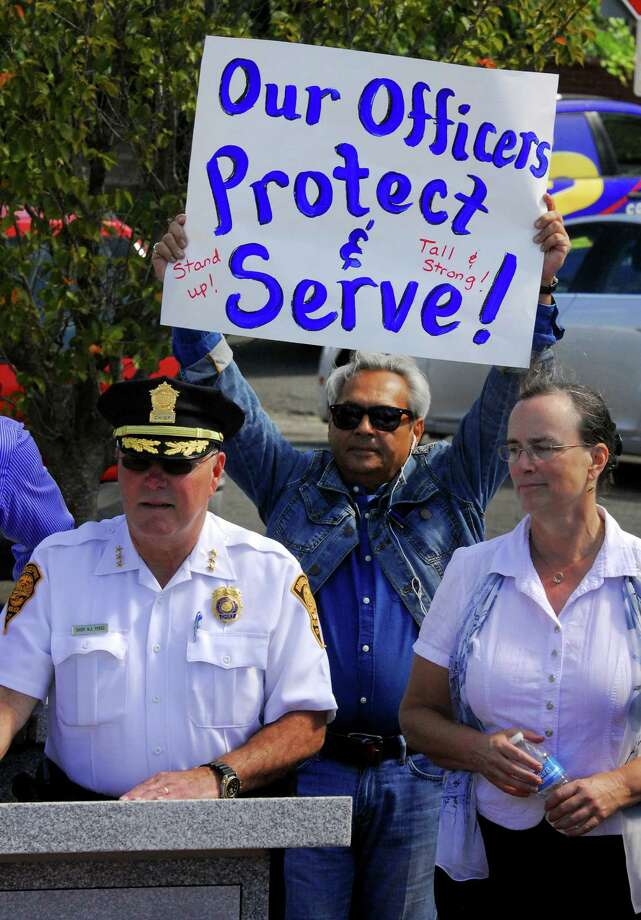 Sam Marks, of Bridgeport, holds up a poster showing his support for Bridgeport Police Officers during a community march in solidarity with the police officers outside of police headquarters in Bridgeport, Conn., on Saturday Sept. 24, 2016. In the foreground at left is Bridgeport Police Chief Armando Perez. Dozens of residents joined members of the department and local clergy and officials at New Hope Missionary Baptist Church on Park Avenue. Everyone proceeded to march to police headquarters nearby. Photo: Christian Abraham, Hearst Connecticut Media / Connecticut Post