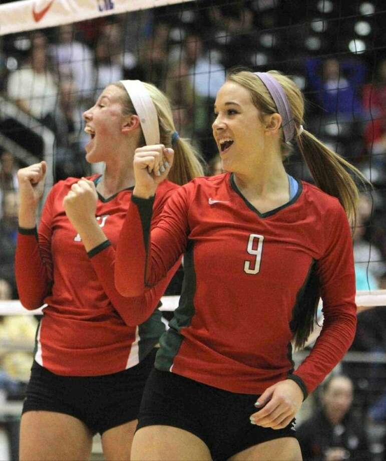 The Woodlands' Courtney Eckenrode (9) and Rachel Reed (12) celebrate a point during a Class 5A UIL Volleyball State Championship game Saturday, Nov. 23, 2013, in Garland, Texas. The Woodlands defeated San Antonio Churchill in straight sets to became the 18th undefeated volleyball state champion in UIL history since 1967. To purchase this photo and other like it, visit HCNPics.com.