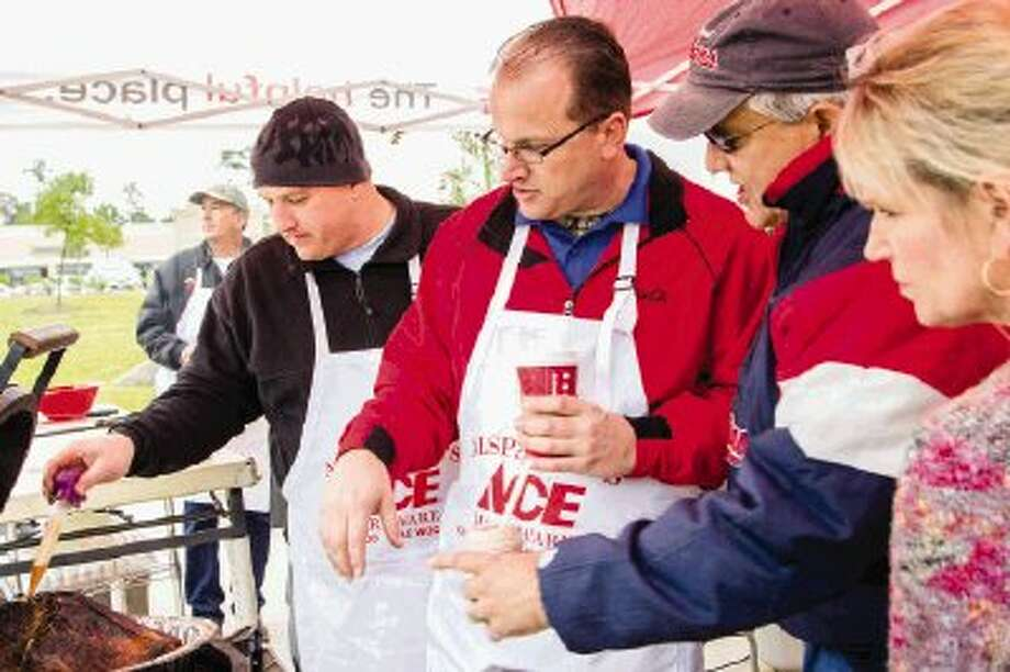 Alspaugh's Ace Hardware of The Woodlands Assistant Manager Nick Davis bastes a turkey while the General Manager Troy Blackmon shows Lisa and Gerry Nemeth a grill during Turkey Fry Day, a cooking demonstrating event featuring various grills on Sunday. / The Conroe Courier/ The Woodland