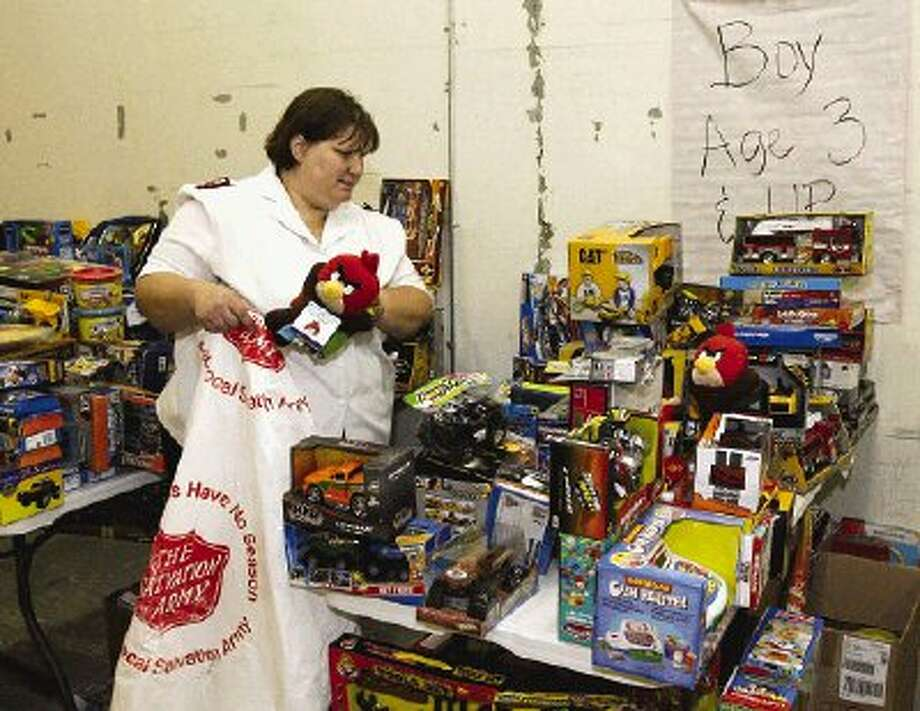 Capt. Karen Twinney with the Salvation Army in Conroe, selects Christmas toys for distribution on Thursday.