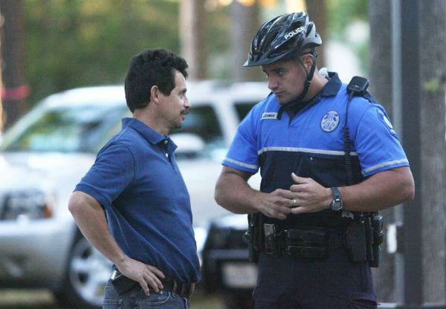Milltown neighborhood resident Martin Ramos speaks with Conroe Police Department officer Christian Lehman during a neighborhood meeting at Milltown Park between residents and the Conroe Police Department Thursday night. / The Courier