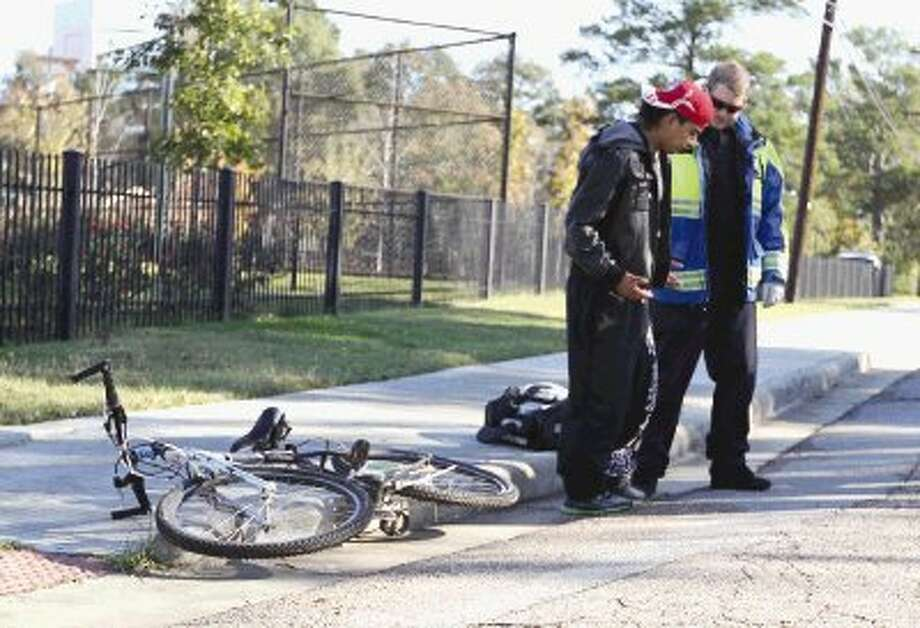 A bicyclist talks with medical personnel after being hit by a truck while riding his bike near Martin Luther King Jr. Park Wednesday morning.