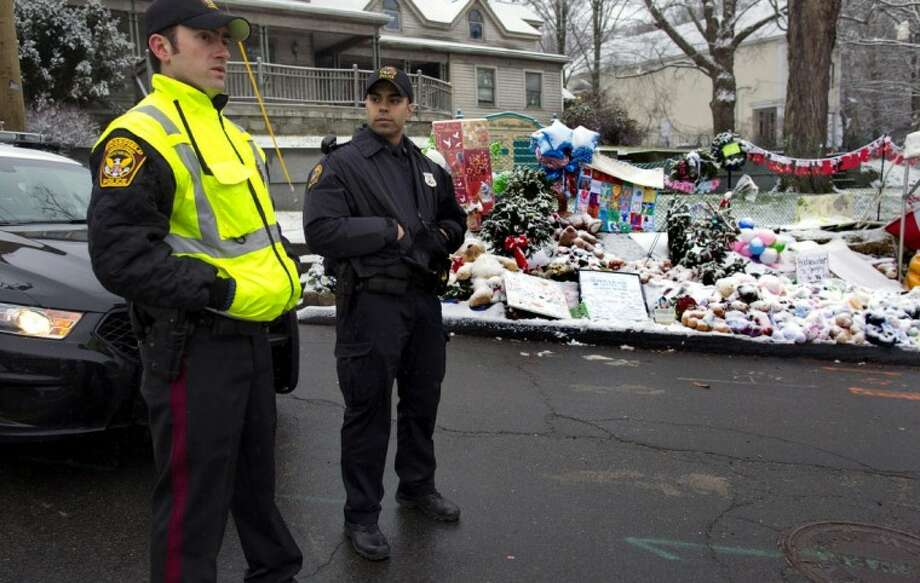 From left, Town of Ridgefield, Conn., Det. Durling, and Town of Greenwich, Conn., Officer Rivera stand near a memorial in Newtown, Conn. Tuesday. Regional police agencies arrived in Newtown to relieve the local police force for the Christmas holiday. Photo: Craig Ruttle