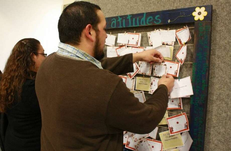 Montgomery United Methodist Church members Jacob and Nicole Torrez hang up their cards of thankfulness.