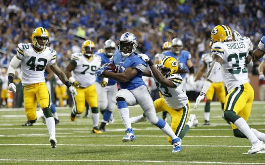 Green Bay Packers defenders close in on Detroit Lions running back Reggie Bush on Thursday at Ford Field in Detroit. Photo: Rick Osentoski