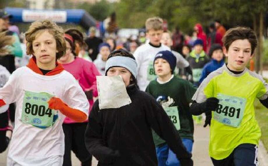 Children participate in the one-mile children's race during the annual Thanksgiving Day Run Thru the Woods in The Woodlands Town Center on a cold Thursday. The South Montgomery County YMCA and GE sponsored this year's event. Go to HCNPics.com to view and purchase this photo, and others like it. / The Conroe Courier/ The Woodland