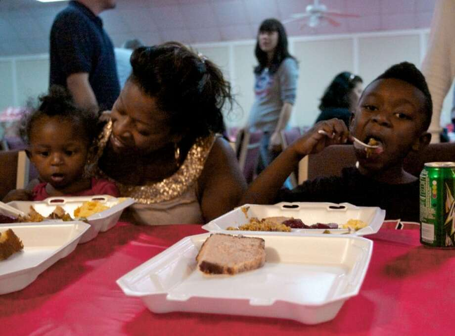 Joanne Moore enjoys a Christmas meal with her 15-month-old daughter Sevenia and son Quinton at The Father's House in Conroe. The church provided free Christmas meals to those in the community along with toys and stocking stuffers for children. Photo: Staff Photo By Eric Swist