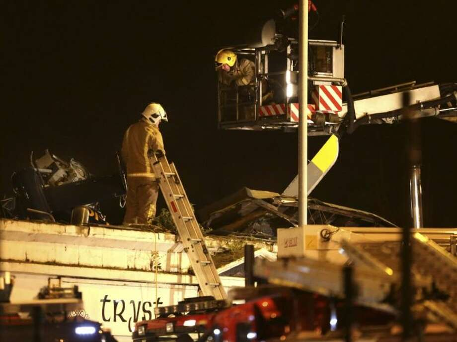 Firefighters inspect the damage at the site of a helicopter crash in Glasgow early Saturday. The police helicopter crashed late Friday night into the roof of a popular pub in Glasgow, Scotland. Photo: Andrew Milligan