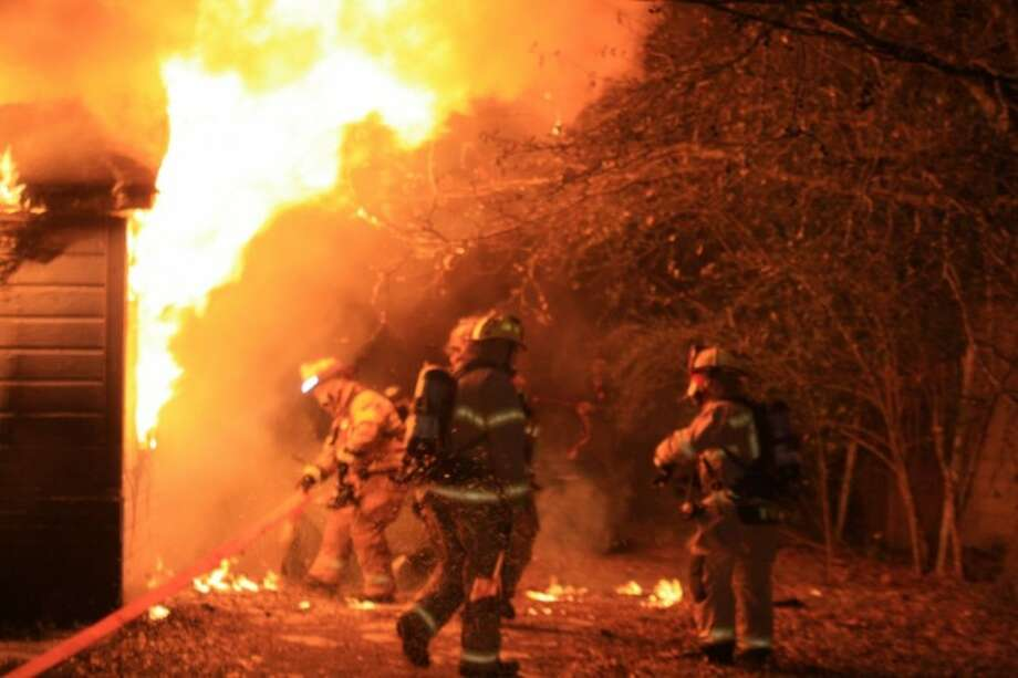 Conroe firefighters battle a blaze that damaged a home on South 1st Street early Friday morning. The 74-year-old homeowner was staying elsewhere when the fire broke out.