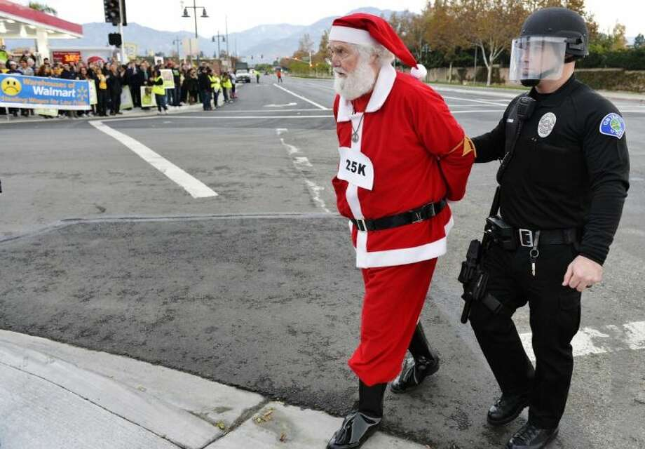 Wal-Mart protester Karl Hilgert, dressed as Santa Claus, is led away after being arrested for failure to disperse after sitting down with nine other protesters in the middle of an intersection on Friday in Ontario, Calif. A labor group and supporters used the Black Friday shopping period for a demonstration over wages and working conditions at Wal-Mart.
