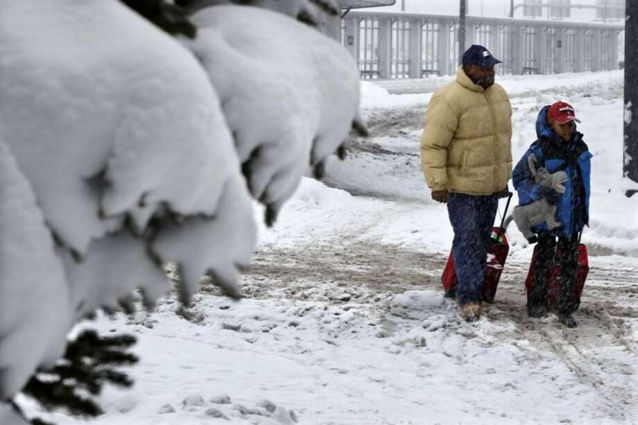 People walk in the snow at Buffalo Niagara International Airport in Buffalo, N.Y., Saturday. A mild but widespread winter storm has developed over the Northeast and the upper Ohio River Valley, the second in less than a week for the regions. Photo: Mel Evans