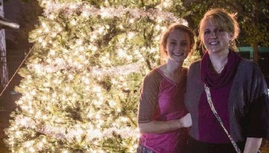 Faith and Jacki Dowling, the daughter and wife of Captain William Dowling, light a tree at Gleannloch Farms in Klein on Saturday night. Captain Dowling was injured six months ago in a hotel fire that took the lives of several firefighters. / The Conroe Courier/ The Woodlands Villager/ The Spring Observer