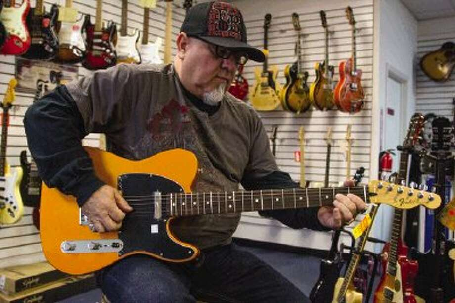 Chip Looney, owner of Guitars & Music Conroe, plays guitar in his store on Tuesday morning. Looney started playing the drums when he was eight but later switched to liking vocals and guitar better. Photo: Staff Photo By Ana Ramirez / The Conroe Courier