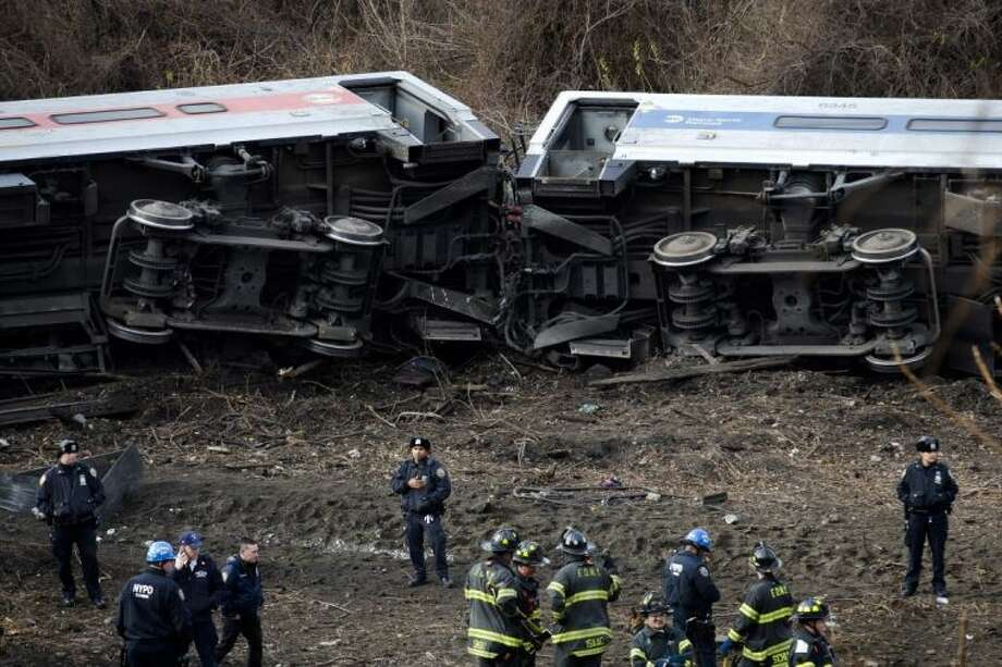 Emergency personnel respond to the scene of a Metro-North passenger train derailment in the Bronx borough of New York Sunday. The train derailed on a curved section of track in the Bronx on Sunday morning, coming to rest just inches from the water and causing multiple fatalities and dozens of injuries, authorities said. Metropolitan Transportation Authority police say the train derailed near the Spuyten Duyvil station. Photo: John Minchillo