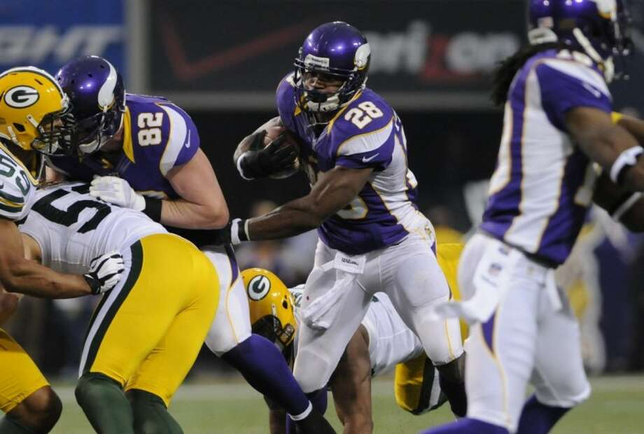 Vikings running back Adrian Peterson became the seventh player in NFL history to rush for 2,000 yards in a single season on Sunday. His team also beat the Packers and is on the way to the NFL playoffs. Photo: Jim Mone