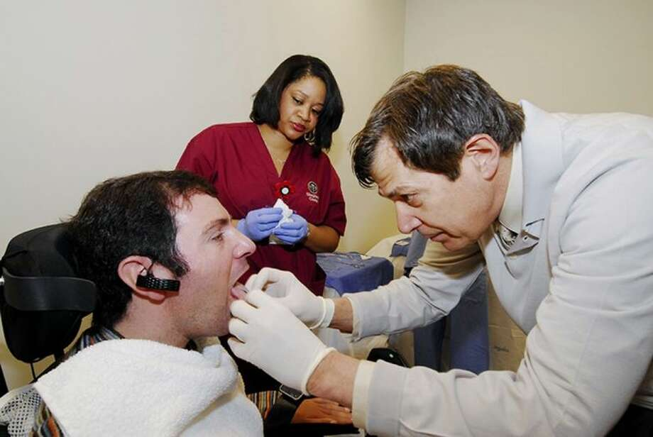 This undated handout photo provided by the Shepherd Center shows Jason DiSanto, left, receiving a tongue piercing at Georgia Tech in Atlanta. An experimental device is letting paralyzed people drive wheelchairs simply by flicking their tongue in the right direction. The Tongue Drive System was developed at Georgia Tech and tested at Shepherd Center in Atlanta. Photo: Gary Meek
