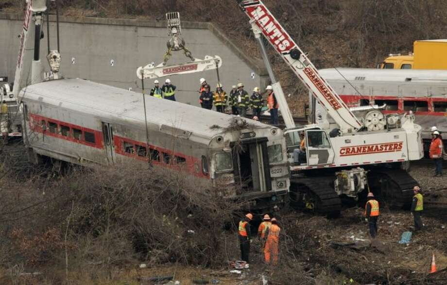 """Cranes salvage the last car from from a train derailment in the Bronx section of New York on Monday. Federal authorities began righting the cars Monday morning as they started an exhaustive investigation into what caused a Metro-North commuter train rounding a riverside curve to derail, killing four people and injuring more than 60 others. A second """"event recorder"""" retrieved from the train may provide information on the speed of the train, how the brakes were applied, and the throttle setting, a member of the National Transportation Safety Board said Monday. Photo: Mark Lennihan"""