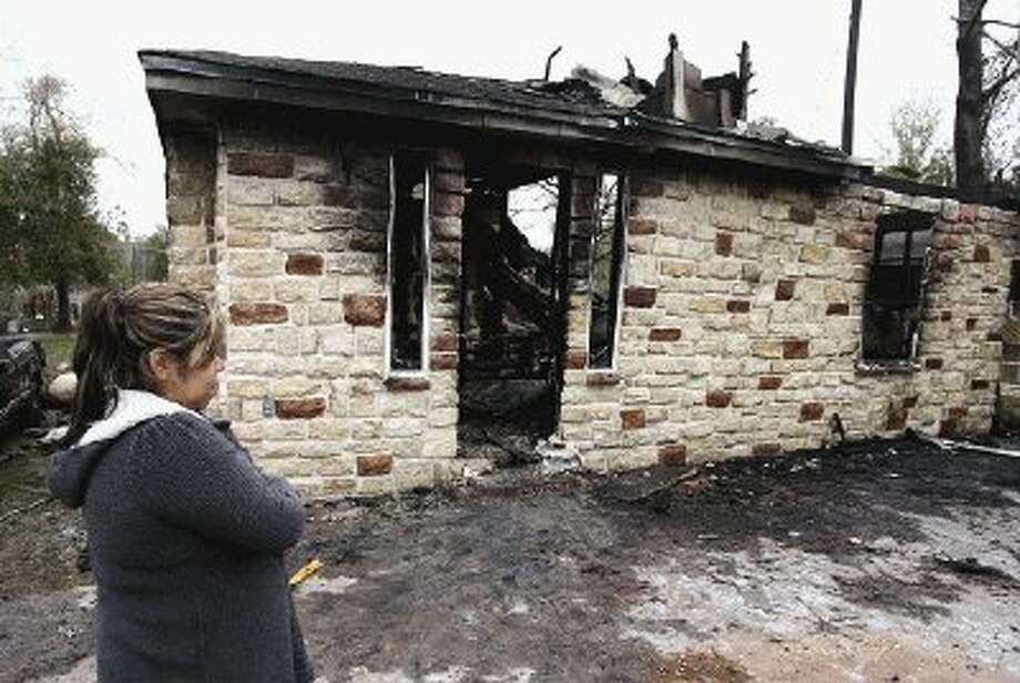 Marisa Bolanos stares at the charred remains of her mother's home that was destroyed by fire early Monday morning on Gladiola off of FM 1314 in Conroe.