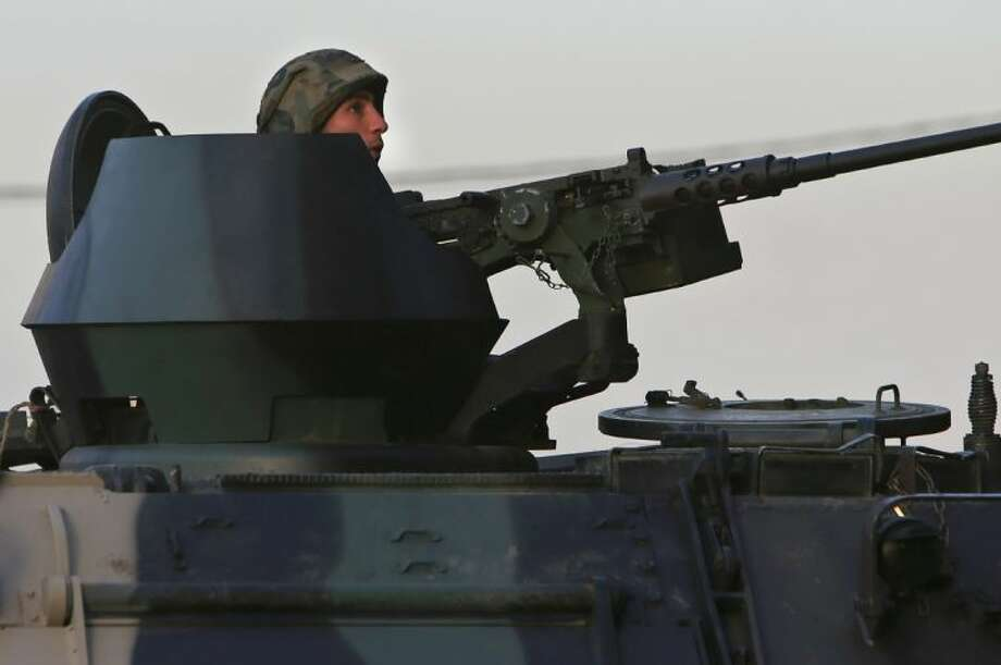 A Lebanese army soldier sits behind his weapon on the top of an armored personnel carrier, during clashes between supporters and opponents of Syrian President Bashar Assad in the northern port city of Tripoli, Lebanon, Monday. Photo: Hussein Malla