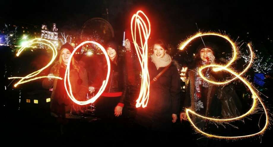 Katy Saunders, left, Alex Mueller, center left, Rebekka Frank and Arina Motamedi, right, play with sparklers ahead of welcoming in the new year during the 2013 Edinburgh Hogmanay celebrations in Scotland Monday. Photo: Danny Lawson