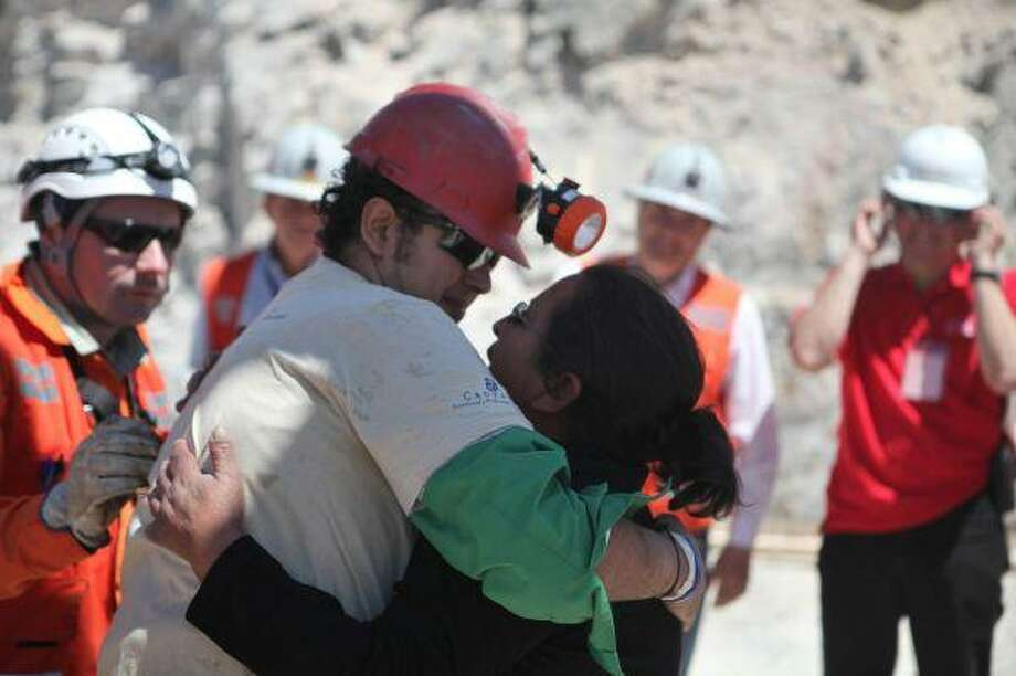 In this photo released by the Government of Chile, miner Daniel Herrera Campos embraces his mother after being rescued from the collapsed San Jose gold and copper mine, near Copiapo, Chile, Wednesday. Herrera was the sixteenth of 33 miners rescued from the mine after more than two months trapped underground. / Government of Chile