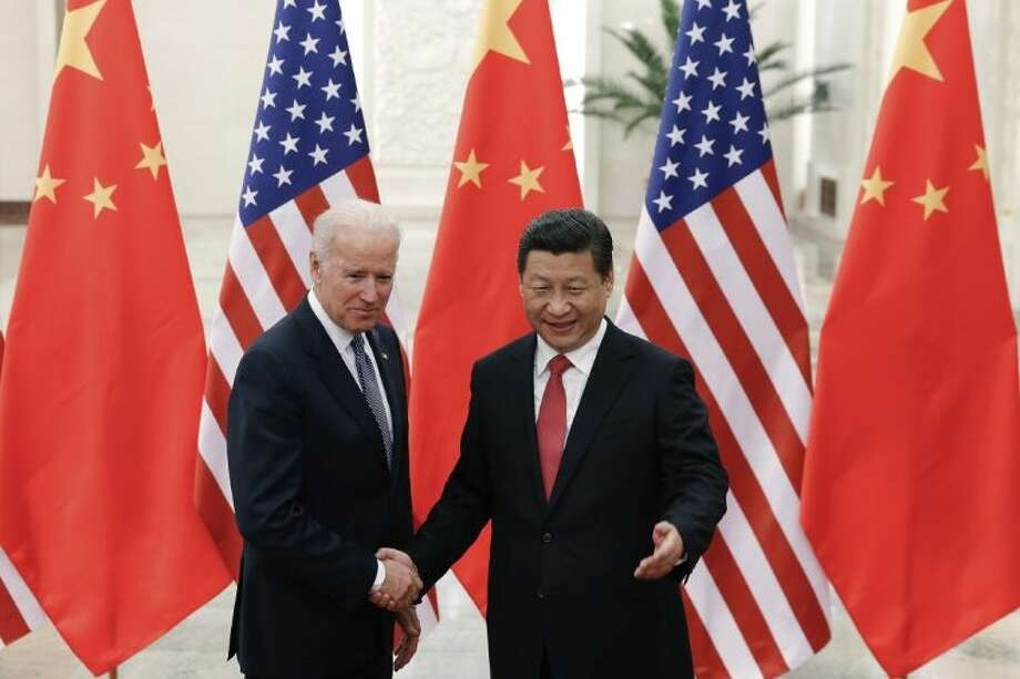 Chinese President Xi Jinping, right, shakes hands with U.S Vice President Joe Biden, left, as they pose for photos at the Great Hall of the People in Beijing, China on Wednesday. Photo: Lintao Zhang