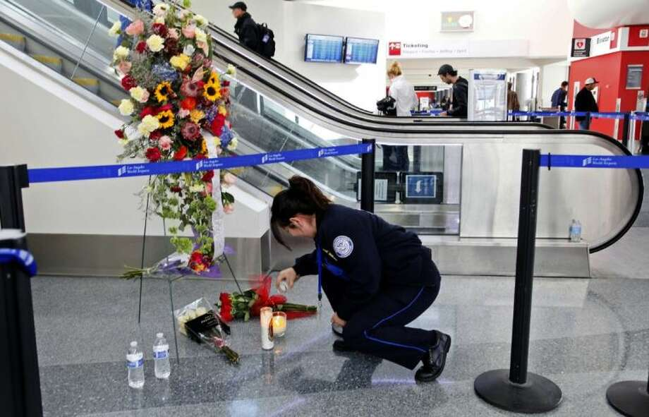 Transportation Security Administration officer Alexa Mendoza lights a candle at a memorial to TSA officers killed and wounded at Terminal 3 at Los Angeles International Airport Monday. TSA Officer Gerardo I. Hernandez was killed and two officers and one civilian wounded in the shooting at Terminal 3 Friday, Nov. 1. Operations at the airport were back to normal Monday, the first business day since the attack. Photo: Nick Ut